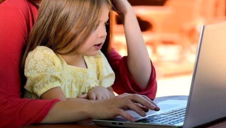 Dziewczynka siedząca na kolanach kobiety przy stole przez laptopem